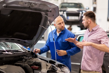 auto service, repair, maintenance and people concept - mechanic with clipboard and man or owner talking at car shop Stock Photo