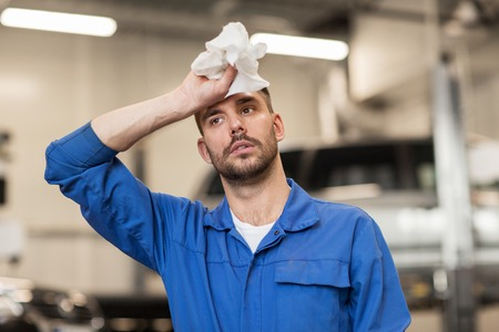 car service, repair, maintenance and people concept - tired auto mechanic man or smith at workshop