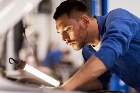 servizio di auto, riparazione, manutenzione e persone Concetto - meccanico uomo con lampada funzionante al workshop