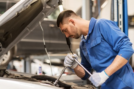 car service, repair, maintenance and people concept - auto mechanic man with wrench and lamp working at workshop 版權商用圖片 - 65130995