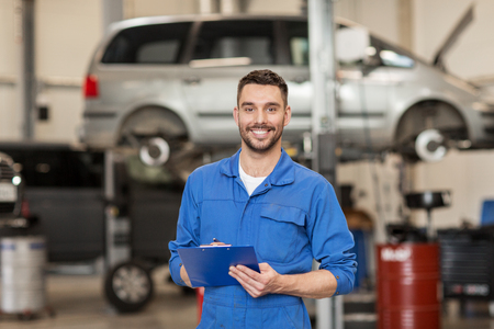auto service, reparatie, onderhoud en mensen concept - gelukkig lachend auto monteur man of smith met klembord op workshop