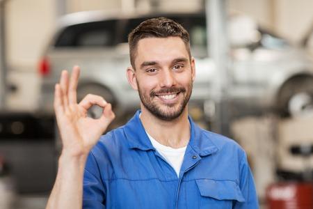 serwis samochodowy, naprawa, konserwacja i ludzie pojęcie - szczęśliwy człowiek uśmiechnięty mechanik samochodowy lub Smith pokazuje ok znak ręką w warsztacie