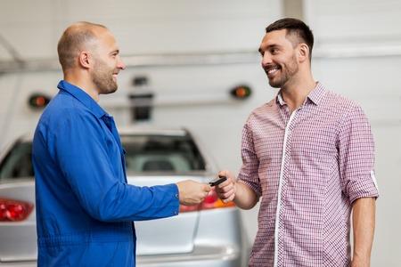 自動サービス、修理、保守および人々 コンセプト - 幸せな笑みを浮かべて男やカーショップでの所有者へキーを与えるクリップボードとメカニック