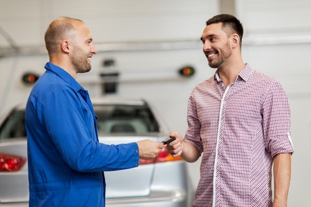 Auto-Service, Reparatur, Wartung und Menschen Konzept - Mechaniker mit Zwischenablage glücklich lächelnde Mann oder Eigentümer im Autogeschäft, die Schlüssel Standard-Bild - 65131003
