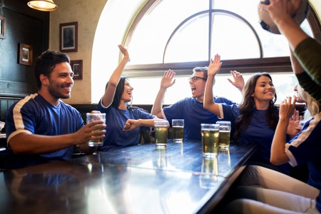 sports bar: sport, people, friendship and entertainment concept - happy football fans or friends drinking beer, making high five and celebrating victory at bar or pub