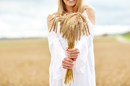 spica: country, nature, summer holidays, vacation and people concept - close up of smiling young woman in white dress with spikelets on cereal field Stock Photo