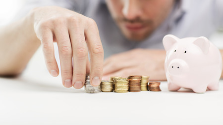 business, people, finances and money saving concept - close up of businessman with piggy bank and coins Imagens