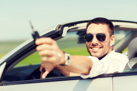 ownerships: auto business, transport, leisure and people concept - happy man in cabriolet showing car key Stock Photo