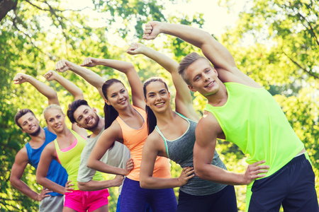 fitness, deporte, la amistad y el concepto de estilo de vida saludable - grupo de amigos o deportistas adolescentes felices que ejercitan y estiran las manos en el campo de entrenamiento