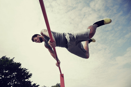 salud y deporte: fitness, sport, training and lifestyle concept - young man exercising on horizontal bar outdoors