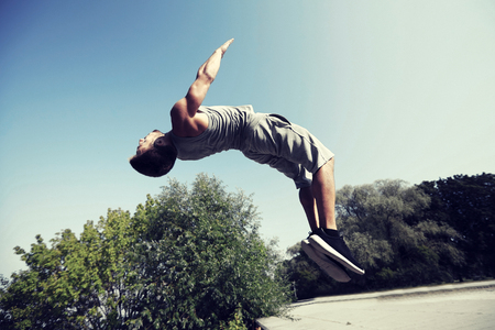 working out: fitness, sport, parkour and people concept - young man jumping in summer park Stock Photo