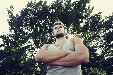 summer sport: fitness, sport, people and healthy lifestyle concept - sporty young man with crossed arms at summer park Stock Photo