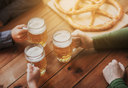 german: people, leisure and drinks concept - close up of male hands with beer mugs and pretzels at bar or pub Stock Photo