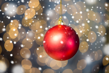 red christmas ball: christmas, decoration, holidays concept - close up of red shiny ball over golden lights background