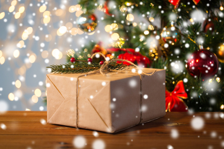 sala parto: christmas, holidays, presents, new year and decor concept - close up of gift box wrapped into brown mail paper and decorated with fir brunch and rope bow over lights background
