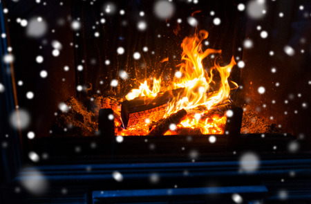 hotbed: winter, christmas, warmth, fire and coziness concept - close up of burning fireplace with snow Stock Photo