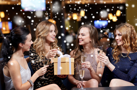 party night: celebration, friends, new year, christmas and winter holidays concept - happy women with champagne glasses and gift box at bachelorette or birthday party at night club over snow Stock Photo