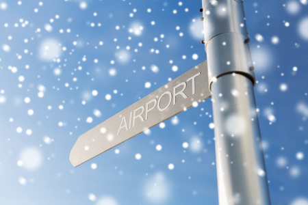 transportation, direction, location, travel and road sign concept - close up of airport signpost over blue sky background with snow Stock Photo