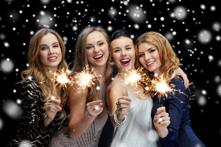 new year party, christmas, winter holidays and people concept - happy young women with sparklers over black background with snow