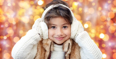 winter, people, christmas and clothing concept - happy little girl wearing earmuffs and gloves over golden holidays lights background Stock Photo
