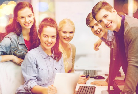 internet education: education, techology and internet concept - group of smiling students with computer monitor and tablet pc