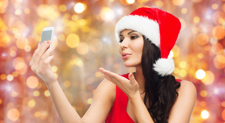 blow kiss: people, holidays, christmas and technology concept - beautiful sexy woman in red santa hat taking selfie picture by smartphone and sending blow kiss to camera over lights background