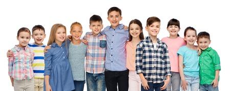 niños sonriendo: la infancia, la moda, la amistad y el concepto de la gente - grupo de niños sonrientes felices abrazos sobre el fondo blanco Foto de archivo