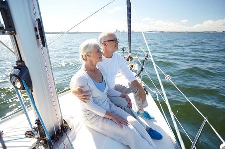 voilier ancien: voile, l'âge, le tourisme, Voyage et les gens concept - heureux personne agee, couple enlacé sur le bateau à voile ou yacht pont flottant en mer