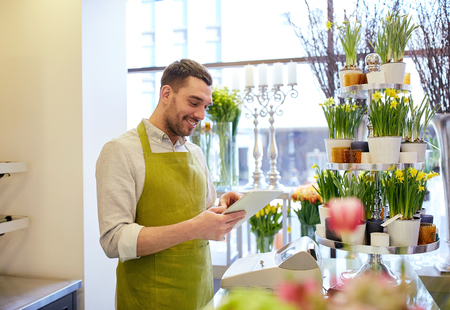 floristry: people, business, technology, sale and floristry and concept - happy smiling florist man with tablet pc computer at flower shop counter Stock Photo