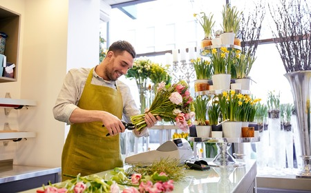 people, business, sale and floristry concept - happy smiling florist man making bunch and cropping stems by scissors at flower shop Stock Photo