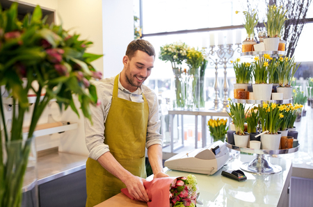 floristry: people, shopping, sale, floristry and consumerism concept - happy smiling florist man wrapping flowers in paper at flower shop Stock Photo