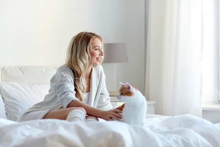 woman in bed: pets, morning, comfort, rest and people concept - happy young woman with cat in bed at home