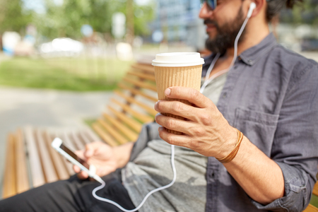 hand paper: people, drinks, technology, leisure and lifestyle - close up of man with earphones and smartphone drinking coffee from disposable paper cup on city street bench Stock Photo