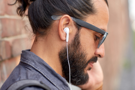 people, technology, leisure and lifestyle - close up of man with earphones listening to music outdoors