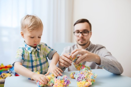 father and son: family, childhood, creativity, activity and people concept - happy father and little son playing with ball clay at home Stock Photo