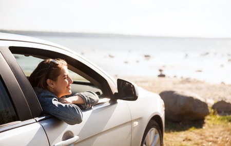 drive car: summer vacation, holidays, travel, road trip and people concept - happy smiling teenage girl or young woman in car at seaside