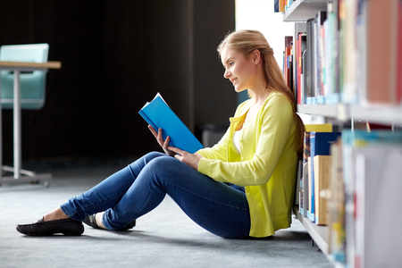women sitting: education, high school, university, learning and people concept - smiling student girl reading book sitting on floor at library