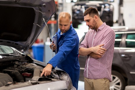 auto service, repair, maintenance and people concept - mechanic with clipboard and man or owner looking at broken car engine at shop Reklamní fotografie