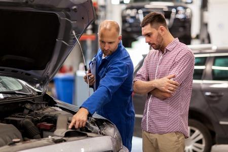 servicio de automóviles, reparación, mantenimiento y concepto de la gente - mecánico con portapapeles y el hombre o el dueño mirando a motor de un coche roto en la tienda Foto de archivo
