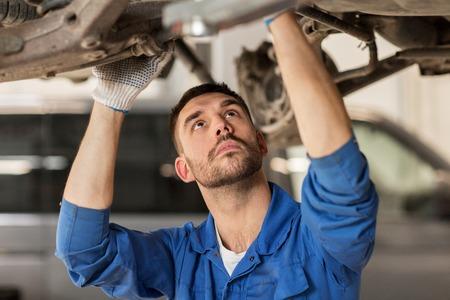 servizio di auto, riparazione, manutenzione e persone Concetto - meccanico uomo o fabbro che lavora al workshop