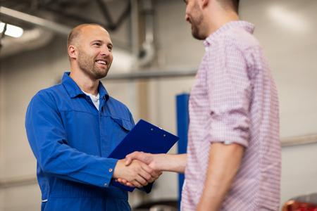 Auto-Service, Reparatur, Wartung, Gestik und Menschen Konzept - Mechaniker mit Zwischenablage und Mann oder Eigentümer Händeschütteln im Autogeschäft