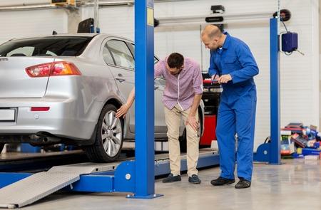 auto usługa, naprawa, utrzymanie i ludzie pojęć, - mechanik z schowkiem, mężczyzna lub właściciel pokazuje koło przy samochodu sklepem Zdjęcie Seryjne