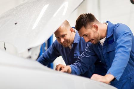 Auto service, reparatie, onderhoud en mensen concept - mechanische mannen met moersleutel reparatie auto op de werkplaats Stockfoto