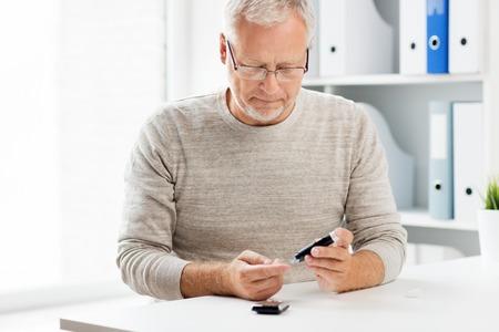 medicina, età, diabete, assistenza sanitaria e concetto di persone anziane - uomo anziano con glucometer controllando il livello di zucchero nel sangue a casa