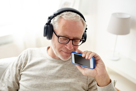 home audio: technology, people, lifestyle and leisure concept - happy senior man with smartphone and headphones listening to music at home
