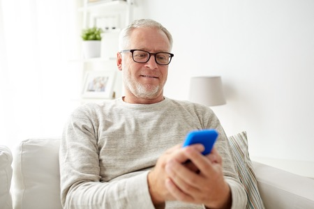 technology, people, lifestyle and communication concept - happy senior man dialing phone number and texting on smartphone at home