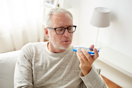using voice: technology, people, lifestyle and communication concept - close up of senior man using voice command recorder or calling on smartphone at home Stock Photo