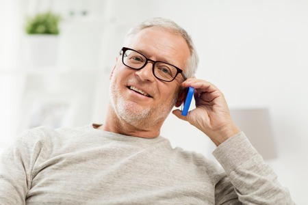 technology, people, lifestyle and communication concept - happy senior man dialing phone number and calling on smartphone at home Фото со стока