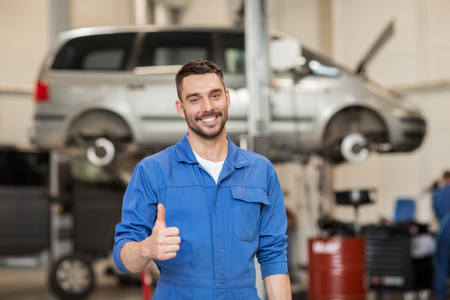 car service, repair, maintenance, gesture and people concept - happy smiling auto mechanic man or smith showing thumbs up at workshop Stockfoto