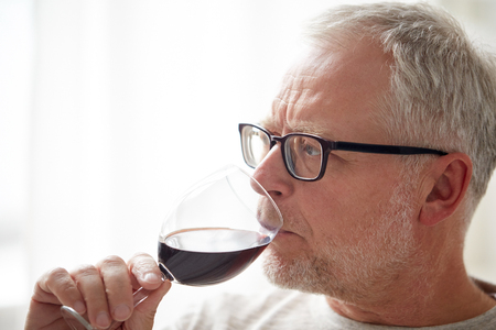 degustating: people, alcohol and drinks concept - close up of senior man drinking red wine from glass at home Stock Photo